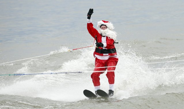 A man dressed as Santa Claus waves to the crowd as he water skis on the Potomac River in Alexandria, Virginia, on Christmas Eve December 24, 2015. (Photo by Kevin Lamarque/Reuters)