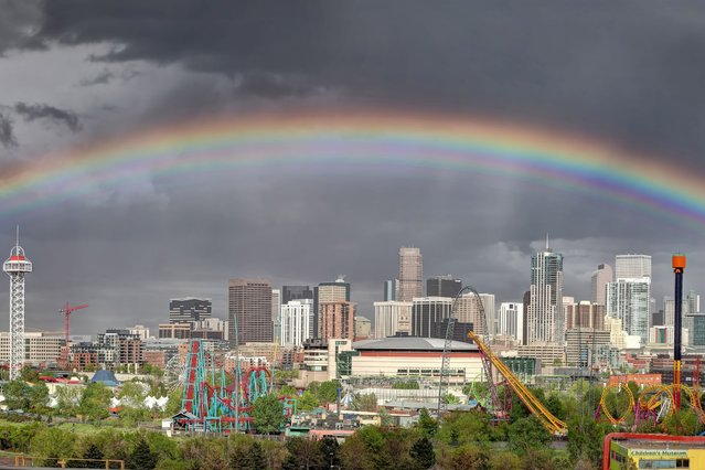 A wide view of a huge rainbow stretching over the city of Denver in Colorado. (Photo by Greg Thow/Barcroft Media)