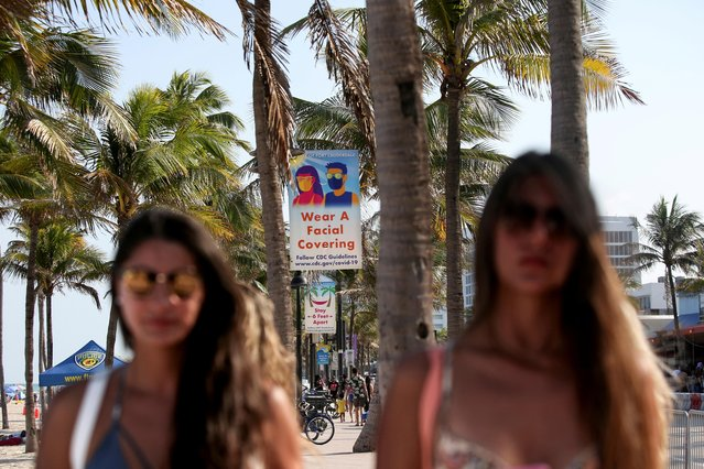 People walk under signs near the beach urging mask-wearing and social distancing during Spring Break in Fort Lauderdale, Florida, U.S., March 24, 2021. (Photo by Yana Paskova/Reuters)