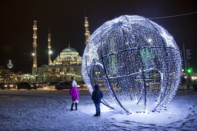 Children stand at a Christmas bauble and a mosque illuminated for New Year celebrations in downtown Grozny, the capital of Chechnya, Russia, Thursday, December 31, 2015. (Photo by Musa Sadulayev/AP Photo)