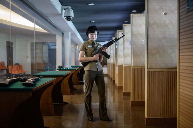 In a photo taken on July 29, 2018 instructor Kim Ju Yang (20) holds a North Korean- made assault rifle as she poses for a portrait at the Meari shooting range in Pyongyang. The Meari shooting range offers customers the opportunity to shoot a number of North Korean and foreign- made firearms, most of which have been modifed to fire .22 calibre ammunition costing one US dollar per round. (Photo by Ed Jones/AFP Photo)