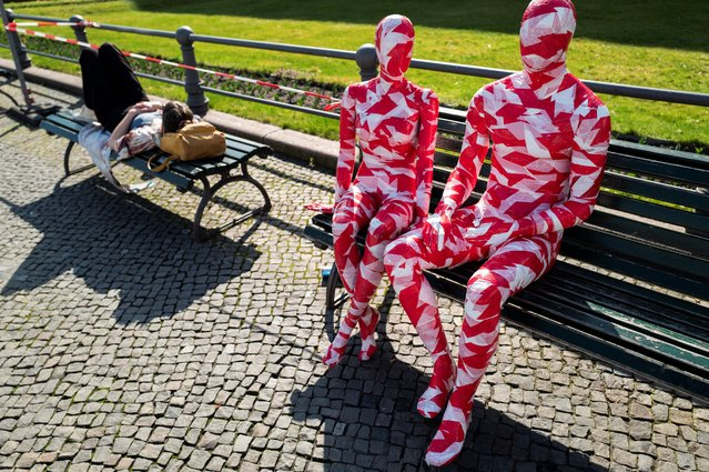 "A woman takes a nap on a bench next to mannequins wrapped in barrier tape near Berlin's landmark Brandenburg Gate on March 31, 2021, as part of German artist Dennis Josef Meseg's Corona Memorial called ""It is Like it is"". The moving exhibition will be set up near various landmarks in the German capital over the next days. (Photo by John MacDougall/AFP Photo)"
