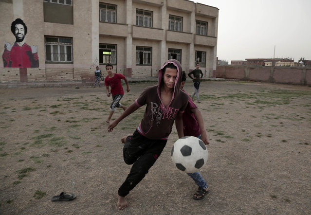 In this May 2, 2018 photo, boys play football at the sports and youth center in Mohamed Salah's hometown Nile delta village of Nagrig, Egypt. Residents boast of how the Liverpool winger has poured millions of pounds into the village, with the beneficiaries' list including a school, a mosque, a youth center and a dialysis machine at a nearby hospital. His success as a footballer in Europe's most attractive league has inspired many parents in Nagrig to send their children to soccer academies in the hope that maybe one day they can emulate his success. (Photo by Nariman El-Mofty/AP Photo)