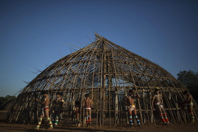 """Waura Indian men wait outside a hut for the start of the ceremonies of this year's """"quarup"""", a ritual held over several days to honour in death a person of great importance to them, in Xingu National Park, Mato Grosso State, August 24, 2013. This year the Waura tribe is honouring their late cacique (chief) Atamai, who died in 2012 and helped created the Xingu Park, and his important contribution in facilitating communication between white Brazilians and Indians. (Photo by Ueslei Marcelino/Reuters)"""