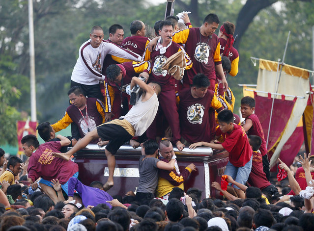A few Catholic devotees manage to get closer to either kiss or rub with towels the cross of the image of the Black Nazarene as they take part in a raucous procession to celebrate its feast day in Manila, Philippines, Saturday, January 9, 2016. (Photo by Bullit Marquez/AP Photo)