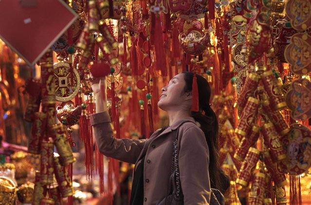 A woman shops for good luck ornaments at the traditional Dihua market for the upcoming Chinese New Year celebrations in Taipei, Taiwan, Monday, February 16, 2015. (Photo by Wally Santana/AP Photo)