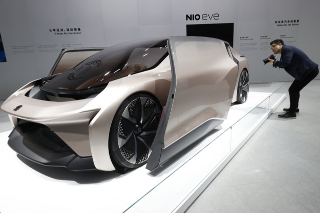 A visitor looks at the NIO eve concept car displayed during the Shanghai Auto Show in Shanghai on Monday, April 19, 2021. (Photo by Ng Han Guan/AP Photo)