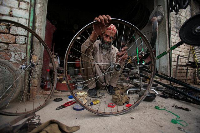 A man repairs a wheel of a bicycle at a shop in Peshawar, Pakistan, November 30, 2016. (Photo by Faisal Mahmood/Reuters)