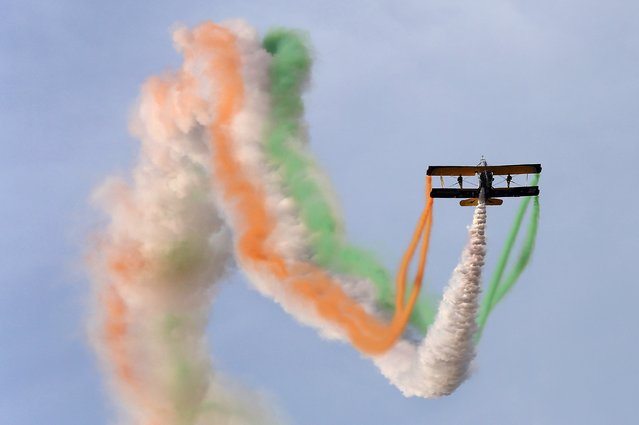 "Catwalk or Skycats of the Scandinavian Aerobatic Team leave a trail of Indian tri-colour smoke as they perform aerobatics during the second day of the ""Aero India 2015"" at the Yelahanka Airforce Station in Bangalore on February 19, 2015. (Photo by Manjunath Kiran/AFP Photo)"