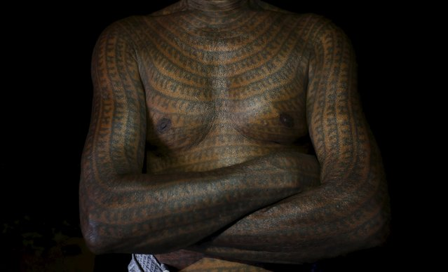 "Mahettar Ram Tandon, 76, a follower of Ramnami Samaj, who has tattooed the name of the Hindu god Ram on his full body, poses for a picture inside his house in the village of Jamgahan, in the eastern state of Chhattisgarh, India, November 17, 2015. ""It was my new birth the day I started having the tattoos,"" Tandon said. ""The old me had died."" ""The young generation just don't feel good about having tattoos on their whole body,"" he added. ""That doesn't mean they don't follow the faith"". (Photo by Adnan Abidi/Reuters)"