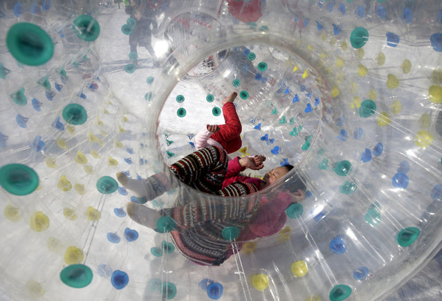 Children play inside an inflatable tube on the snow at Taoranting Park's temple fair for Lunar New Year celebrations in Beijing Monday, February 23, 2015. (Photo by Andy Wong/AP Photo)