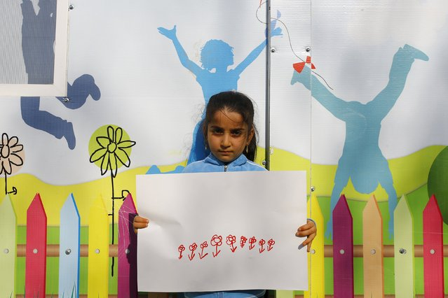 Syrian refugee girl Reyyan Emin, 7, shows her drawing in Yayladagi refugee camp in Hatay province near the Turkish-Syrian border, Turkey, December 15, 2015. (Photo by Umit Bektas/Reuters)