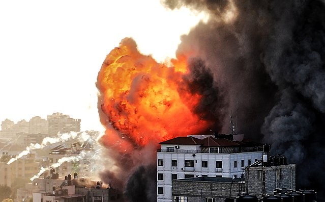"""Smoke rises from 14-story building as Israeli fighter jets continue to pound a Palestinian building called """"Ash-Shuruq"""" at Omar Al-Mukhtar neighbourhood in the Gaza Strip, on May 12, 2021. (Photo by Ali Jadallah/Anadolu Agency via Getty Images)"""
