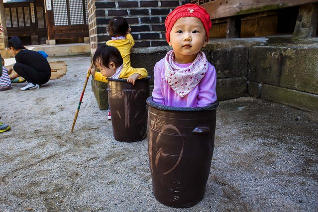 """Jung Ha-yoon, 2, appears to be stuck inside a ceramic container while playing with other children at the traditional sports square during the """"Taste Korea! Korean Royal Cuisine Festival"""" held at Unhyeon Palace in Seoul, South Korea, on October 1, 2013. (Photo by Jacquelyn Martin/Associated Press)"""