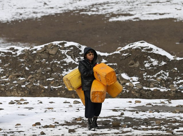 An Afghan boy carries empty water containers as he looks for water on a cold day in Kabul January 25, 2015. (Photo by Mohammad Ismail/Reuters)