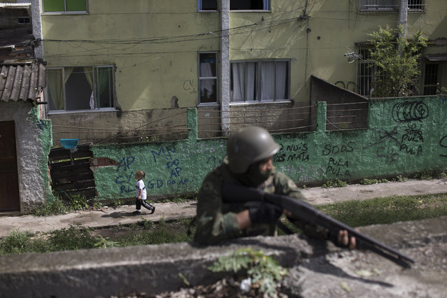 In this February 7, 2018 file photo, a girl runs past soldier with his weapon drawn, during a surprise operation in the City of God slum of Rio de Janeiro, Brazil. Brazil's Public Security Minister Raul Jungmann said said in an interview with the Folha de S. Paulo newspaper on Saturday, August 18, that the military will no longer be in charge of security forces in Rio de Janeiro state as of December. (Photo by Leo Correa/AP Photo)