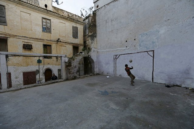 A boy plays with a soccer ball in a playground, where a house previously stood, in the old city of Algiers Al Casbah, Algeria December 2, 2015. (Photo by Zohra Bensemra/Reuters)