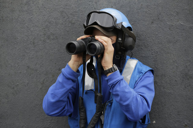 In this Tuesday, March 17, 2015 photo, a French sailor looks with binoculars from the flight deck of the French Navy aircraft carrier Charles de Gaulle in the Persian Gulf. (Photo by Hasan Jamali/AP Photo)