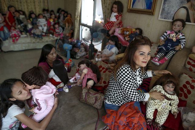"Devotees play with ""child angel"" dolls at a house in Nonthaburi, Thailand, January 26, 2016. A craze for lifelike dolls thought to bring good luck is sweeping Thailand, reflecting widespread anxiety as the economy struggles and political uncertainty persists nearly two years after a coup. (Photo by Athit Perawongmetha/Reuters)"