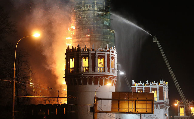 Firefighters battle with a fire in Novodevichy Convent's bell tower in Moscow, Russia, 15 March 2015. The Novodevichy Convent which was built in 1524 is a UNESCO World Heritage site. (Photo by Yuri Kochetkov/EPA)