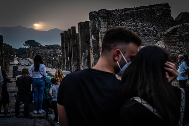 People observe the sunrise on the day of the summer solstice, in Pompei, near Naples, southern Italy, 21 June 2021. The archeological site's extraordinary opening at 4:45 am on the day allowed visitors to see the sunrise aligned with a network of streets in Pompeii. (Photo by Cesare Abbate/EPA/EFE)