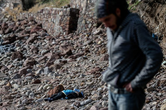 A man stands next to the body of a migrant child washed up on a beach in Canakkale's Bademli district on January 30, 2016 after at least 37 migrants drowned when their boat sank in the Aegean Sea while trying to cross from Turkey to Greece, Turkey's state-run Anatolia news agency reported. The migrants, who included those from Myanmar, Afghanistan and Syria, set sail from the Canakkale province to reach the nearby Greek island of Lesbos, Anatolia said. (Photo by Ozan Kose/AFP Photo)