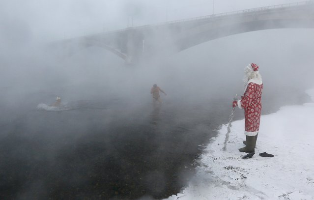 A man dressed as Ded Moroz, the Russian equivalent of Santa Claus, watches Ivan Abrosimov, 80, (L) and Nikolay Bocharov, 78, members of the Cryophile amateurs winter swimmers club, taking a bath in the icy waters of the Yenisei River during the celebrations for the upcoming Christmas and New Year, with the air temperature at about minus 34 degrees Celsius (minus 29.2 degrees Fahrenheit), in Krasnoyarsk, Russia, December 24, 2016. (Photo by Ilya Naymushin/Reuters)
