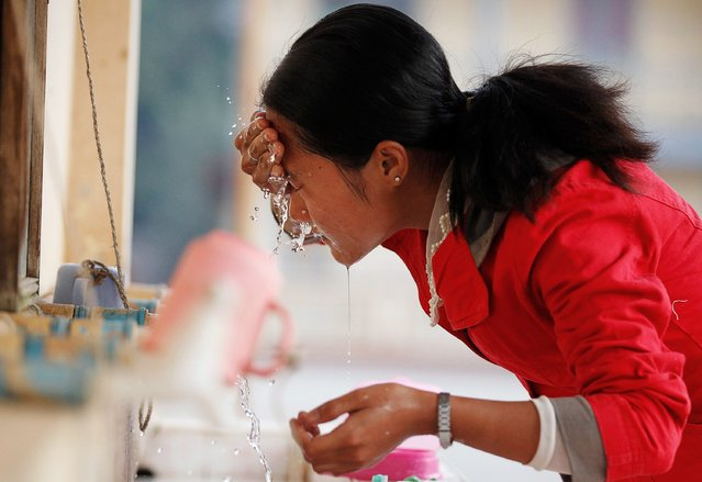 A woman who fled from violence in Laukkai, Kokang region, washes her face at a temporary refugee camp set up in a monastery in Lashio February 19, 2015. (Photo by Soe Zeya Tun/Reuters)