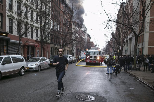 A man runs away from the site of a building fire in the East Village neighborhood of New York City on March 26, 2015. (Photo by Ben Hider/Reuters)