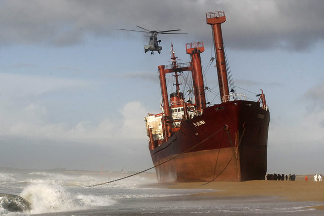 Rescue workers stand next to TK Bremen cargo ship which ran aground during a powerful storm, spilling oil off the coast of France's northwestern region of Brittany as it lies stranded on Kerminihy beach in Erdeven, on December 16, 2011. (Photo by Damien Meyer/AFP Photo)