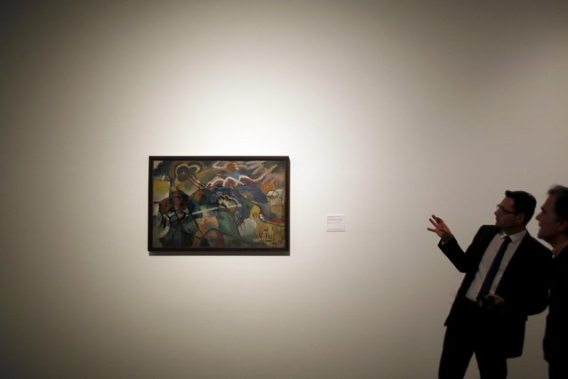 """Men look at """"Composition with white border"""" by Russian-born artist Wassily Kandinsky during an international press tour of the Malaga branch of the State Museum of Russian Art of St Petersburg, a day before its inauguration in Malaga, southern Spain March 24, 2015. (Photo by Jon Nazca/Reuters)"""