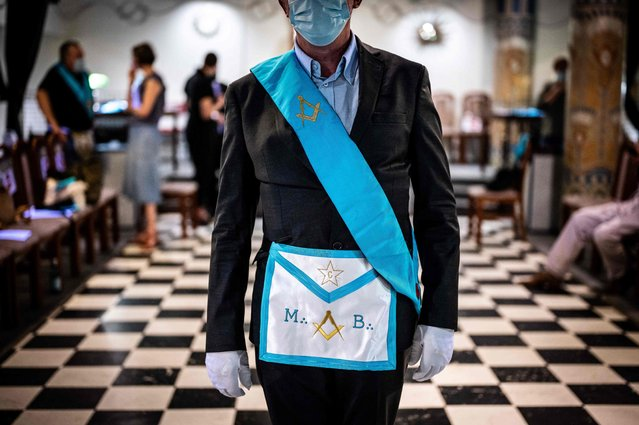 A member of the Grande Loge Mixte de France poses with masonic apparel, in Paris, on June 18, 2021. With a suspended or reduced activity, Freemasonry has been tested by the health crisis but tries to bounce back with reinvented rituals here, there a radio program, or even by wondering about post-Covid society. (Photo by Martin Bureau/AFP Photo)