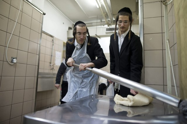 Ultra-Orthodox Jews knead dough in a bakery in an Orthodox neighborhood in Jerusalem, 29 March 2015. Matzah, or unleavened bread, is used instead of bread during the week-long Jewish holiday of Passover, commemorating the Jewish exodus from Egypt in Biblical times. (Photo by Abir Sultan/EPA)