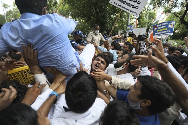 Congress party workers help their leader cross over a police barricade during a protest accusing Prime Minister Narendra Modi's government of using military-grade spyware to monitor political opponents, journalists and activists in New Delhi, India, Tuesday, July 20, 2021. The protests came after an investigation by a global media consortium was published on Sunday. Based on leaked targeting data, the findings provided evidence that the spyware from Israel-based NSO Group, the world's most infamous hacker-for-hire company, was used to allegedly infiltrate devices belonging to a range of targets, including journalists, activists and political opponents in 50 countries. (Photo by Manish Swarup/AP Photo)