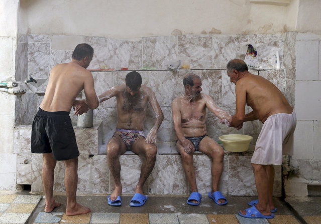 In this Friday, November 21, 2014 photo, bathhouse workers Reza Bagheri, 75, and Heidar Javadi, 39, help two men to bathe at the Setareh public bathhouse, in Yazd, Iran. (Photo by Ebrahim Noroozi/AP Photo)