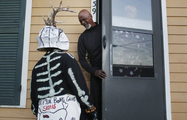 A member of the North Side Skull & Bone Gang, talks to a resident during the wake up call for Mardi Gras, Tuesday, February 9, 2016, in New Orleans. (Photo by Brynn Anderson/AP Photo)
