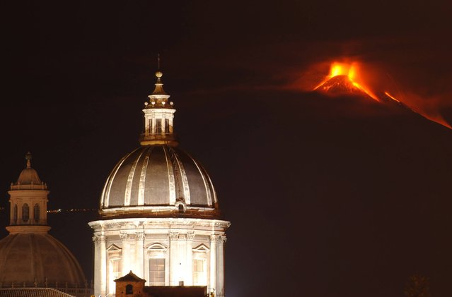 Mt. Etna is seen behind two cupolas as it spews lava during an eruption near the Sicilian town of Catania, Italy, late Thursday, November 28, 2013. Etna's eruptions aren't infrequent, the last one occurred on November 23. (Photo by Salvatore Allegra/AP Photo)