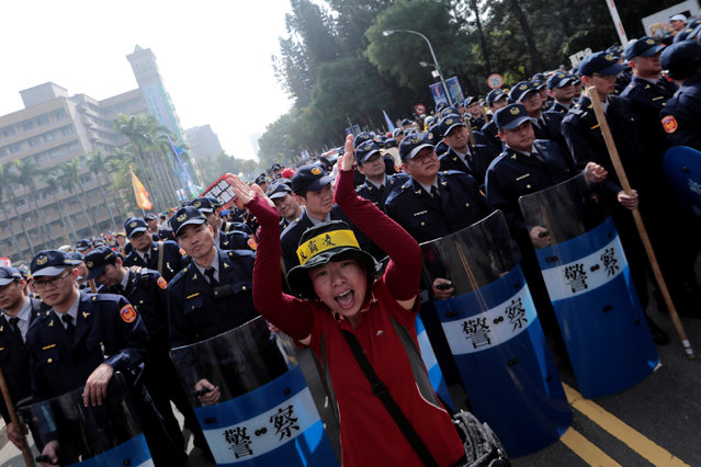 A protester shouts in front of police during a rally against overhaul of the military and civil service pension funds in Taichung, Taiwan January 7, 2017. (Photo by Tyrone Siu/Reuters)