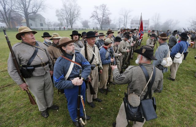 Confederate troops muster in front of the McLean House as they prepare for battle during a re-enactment of the Battle of Appomattox Courthouse as part of commemoration of the 150th anniversary of the surrender of the Army of Northern Virginia at Appomattox Court House in Appomattox, Va., Thursday, April 9, 2015. (Photo by Steve Helber/AP Photo)