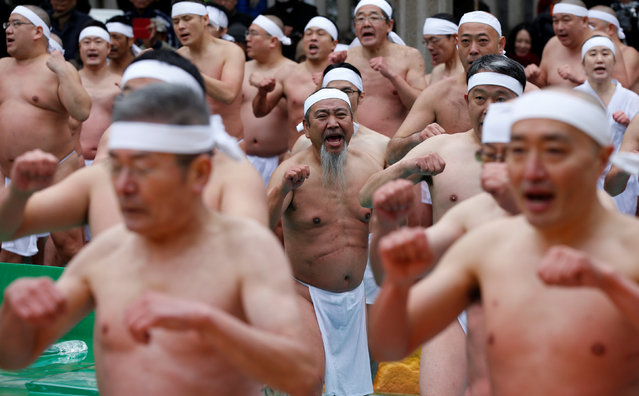 """Men wearing the traditional """"fundoshi"""" or loin cloth warm up before bathing in ice-cold water outside the Teppozu Inari shrine in Tokyo, Japan, January 8, 2017. (Photo by Toru Hanai/Reuters)"""