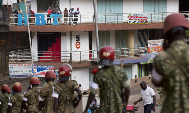 Ugandans look down from a balcony as military police deploy, shortly after the election result was announced, in downtown Kampala, Uganda, Saturday, February 20, 2016. (Photo by Ben Curtis/AP Photo)