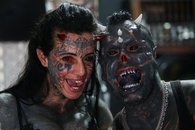 Brazilian tattoo artist Michel Praddo, also known as Diabao or Human Satan, and his wife Carol Praddo, known as Mulher Demonia or Demon Woman, pose in their studio in Praia Grande, Brazil on August 18, 2021. (Photo by Carla Carniel/Reuters)