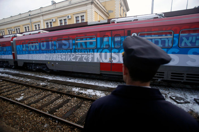 """A railroad worker stands by the first train decorated with letters that read """"Kosovo is Serbian"""" written in twenty languages departing from the Belgrade to Mitrovica, Kosovo at Belgrade's railway station, Serbia, Saturday, January 14, 2017. Serbia has launched a railway link to Serb-dominated northern Kosovo despite protests from authorities in Pristina who described the move as a provocation and an aggressive violation of Kosovo's sovereignty. (Photo by Darko Vojinovic/AP Photo)"""