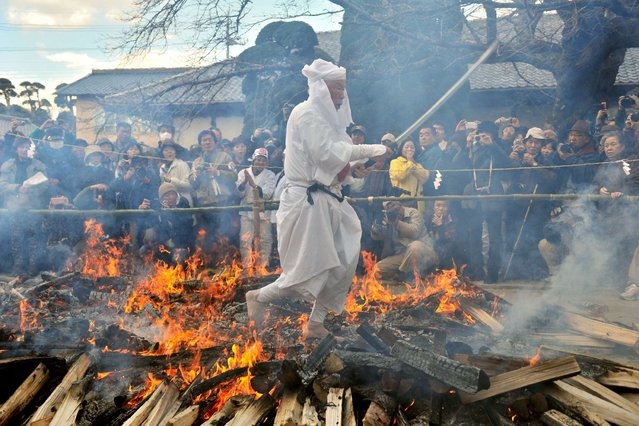 A Shinto priest walks across embers during a fire walking ceremony to pray for good health and safety life at Kabasan Saenazumi Jinja shrine in Sakuragawa City, Ibaraki Prefecture on December 22, 2013. The shrine held the festival every year on the day of the winter. (Photo by Kazuhiro Nogi/AFP Photo)