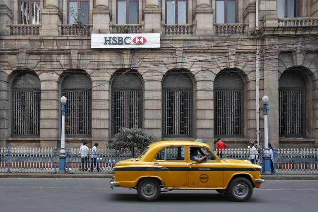A yellow ambassador taxi drives past the HSBC bank building in Kolkata in this November 5, 2013 file photo.  HSBC is expected to report results this week. (Photo by Rupak De Chowdhuri/Reuters)