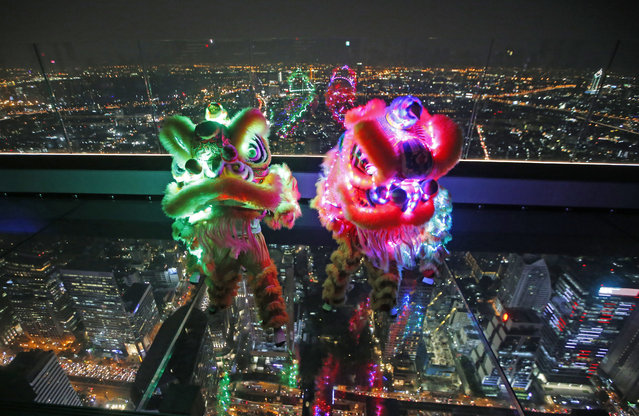 Lion dance with LED lights, perform on the glass deck of the King Power Mahanakhon building, currently Thailand's tallest at 314 meters (1,030 feet) tall, Bangkok, Thailand, Monday, February 4, 2019. Chinese will celebrate the lunar new year on Feb. 5 this year which marks the Year of the Pig in the Chinese zodiac. (Photo by Sakchai Lalit/AP Photo)