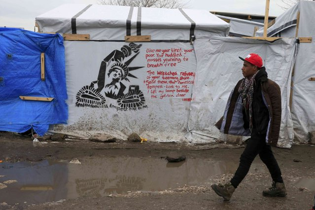 """A migrant walks past a stencil graffiti with a statue of liberty and the message, """"Send the Homless, Tempest tost to me"""", in the southern part of a camp for migrants called the """"jungle"""", in Calais, northern France, February 23, 2016. French authorities have asked migrants living in tents and makeshift shelters in the southern sector of the """"jungle"""", to evacuate the area. (Photo by Pascal Rossignol/Reuters)"""