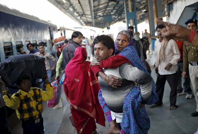 A man carries his mother to board a passenger train at a railway station in New Delhi, India, February 25, 2016. (Photo by Anindito Mukherjee/Reuters)