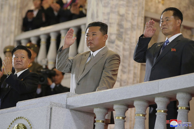 In this photo provided by the North Korean government, North Korean leader Kim Jong Un, center, waves from a balcony toward the assembled troops and spectators during a celebration of the nation's 73rd anniversary at Kim Il Sung Square in Pyongyang, North Korea, early Thursday, September 9, 2021. (Photo by Korean Central News Agency/Korea News Service via AP Photo)