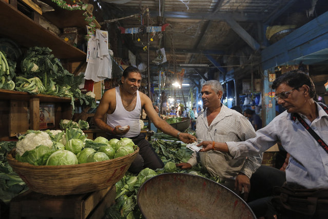 A vendor returns change to a customer at his stall at a wholesale vegetable and fruit market in Mumbai, India, February 29, 2016. (Photo by Danish Siddiqui/Reuters)